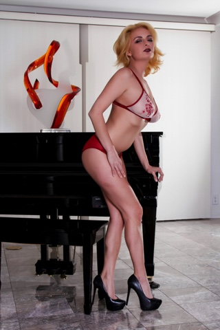 Cute blonde Ashlee Graham poses by the piano